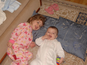Abby and Rebekah lounging in their pajamas.