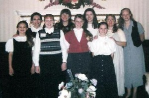 Jessica Steele is in the front wearing a striped sweater vest. Mrs. Steele and I are next to each other on the back row, directly under the flower arrangement on the wall.