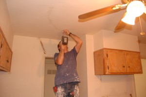 Anthony Courter repairs drywall in our kitchen.