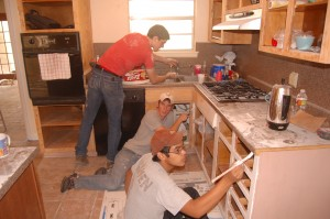 Painting the kitchen cabinets. From the top: Aaron Courter, Jeremy Steele, Steven Nguyen