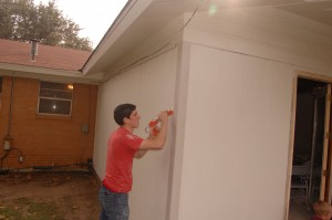 Aaron Courter caulks the new siding at the back of the house.