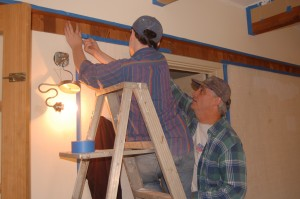 Rick Howard (right) and his son put up masking tape in preparation for painting the walls.